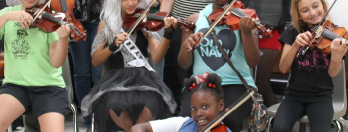 Bahama Village Music Program teachers Shana Gaskill, Angela Mingo, Marci Rose, with CFFK Vice Chairman and Grant Committee Chair Ann Reynolds, BVMP Executive Director Katchen Duncan, and students in the string program.